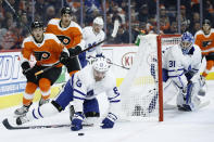 Toronto Maple Leafs' Cody Ceci (83) tries to clear the puck as Philadelphia Flyers' Morgan Frost (48) and James van Riemsdyk (25) pursue during the second period of an NHL hockey game, Tuesday, Dec. 3, 2019, in Philadelphia. (AP Photo/Matt Slocum)