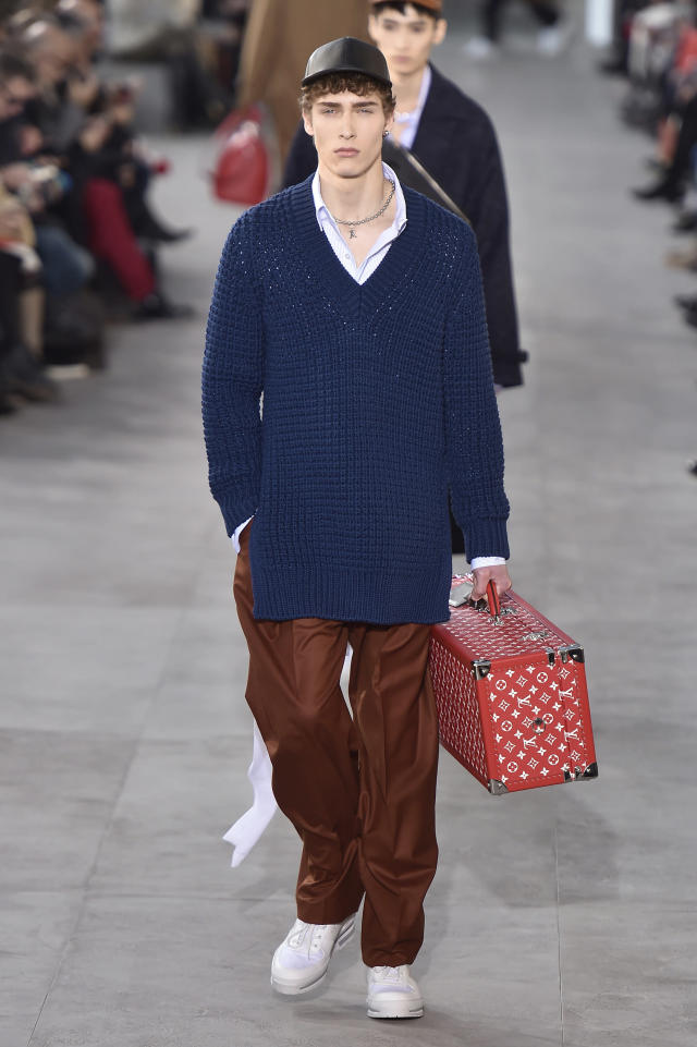 "<p>Another major item from the Louis Vuitton x Supreme collection was the monogram trunk juxtaposed by a very ""hypebeast"" style outfit: baseball cap, oversized sweater, baggy trousers, and crisp white sneakers. (Photo: Catwalking) </p>"