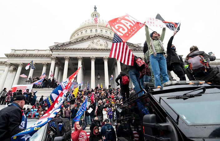 Supporters of Donald Trump stand on a U.S. Capitol Police armored vehicle as others take over the steps of the Capitol on Jan. 6. (Photo: Bill Clark via Getty Images)