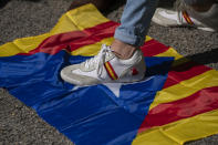 """An """"estelada"""" or Catalonia independence flag is see under the foot of a demonstrator during a celebration for Spain's National Day in Barcelona, Spain, Tuesday, Oct. 12, 2021. Spain commemorates Christopher Columbus' arrival in the New World and also Spain's armed forces day. (AP Photo/Joan Mateu Parra)"""