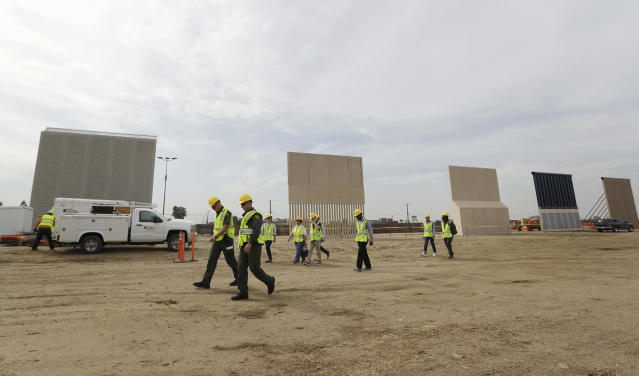 <p>People pass border wall prototypes as they stand near the border with Tijuana, Mexico, Thursday, Oct. 19, 2017, in San Diego, Calif. (Photo: Gregory Bull/AP) </p>