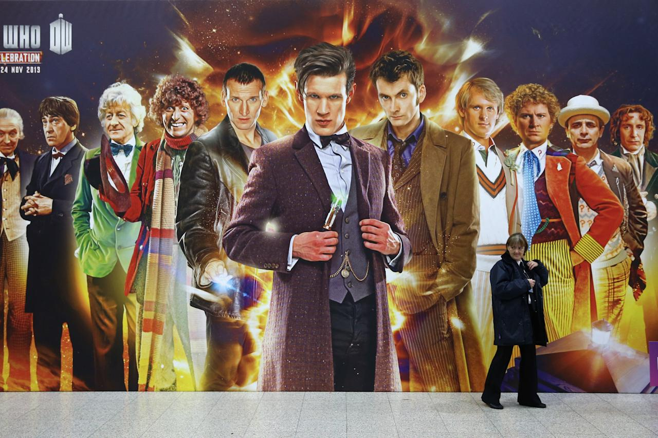 LONDON, ENGLAND - NOVEMBER 22: A security guard walks past a giant Doctor Who poster at the 'Doctor Who 50th Celebration' event in the ExCeL centre on November 22, 2013 in London, England. The sold-out three day event in the ExCeL London convention centre celebrates 50 years of the show which has seen 11 actors play the role of Doctor Who and receives a worldwide cult following. (Photo by Oli Scarff/Getty Images)