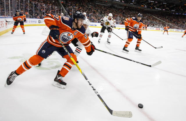 Chicago Blackhawks' Carl Dahlstrom (63) chases Edmonton Oilers' Connor McDavid (97) during the second period of an NHL hockey game Tuesday, Feb. 5, 2019, in Edmonton, Alberta. (Jason Franson/The Canadian Press via AP)
