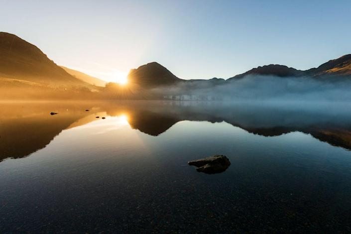 <p>A sunrise fog rolls in over Buttermere lake in the English Lake District of North West England.</p>