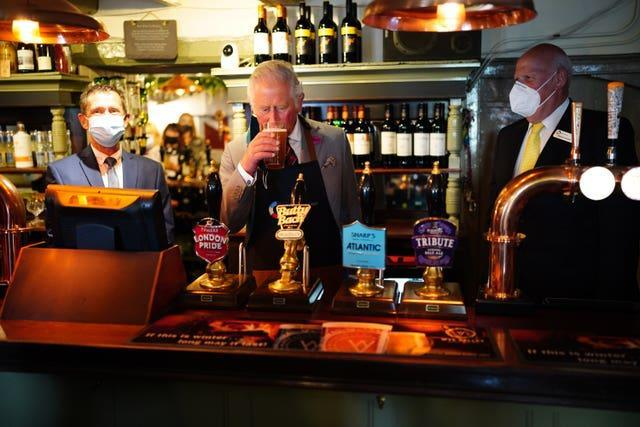 The Prince of Wales tries some Butty Bach (a Welsh term meaning 'little friend') ale during a visit to Ponthir House Inn (Ben Birchall/PA)