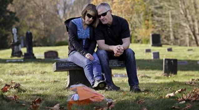 Linda and Rob Robertson visit the grave of their son Ryan. Photo: AP