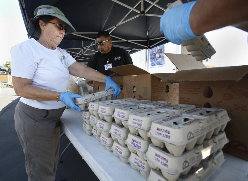 In this photo taken Wednesday, June 5, 2013, Sacramento Food Bank Volunteer Karen Bishop stacks cartons of eggs for distribution in Sacramento, Calif. The Sacramento Food Bank is one of the nations' first farm-to-fork food banks using local growers to provide healthier food to it's clients.(AP Photo/Rich Pedroncelli)