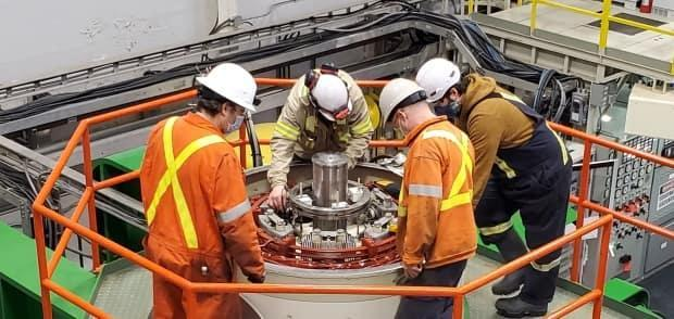 Workers inspect the Snare Rapids hydro unit. The Northwest Territories Power Corporation says they don't know when the facility will be back online.