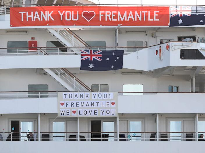 "The MV Artania is seen with ""Thank You Fremantle"" banners and Australian flags positioned on the side of the vessel at the Fremantle Passenger Terminal on March 28, 2020."