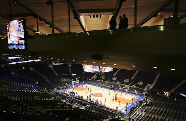 Pedestrians move across one of two Chase Bridges while teams warm up before an NBA basketball game between the New York Knicks and the Charlotte Bobcats, Friday, Oct. 25, 2013, in New York. (AP Photo/Frank Franklin II)