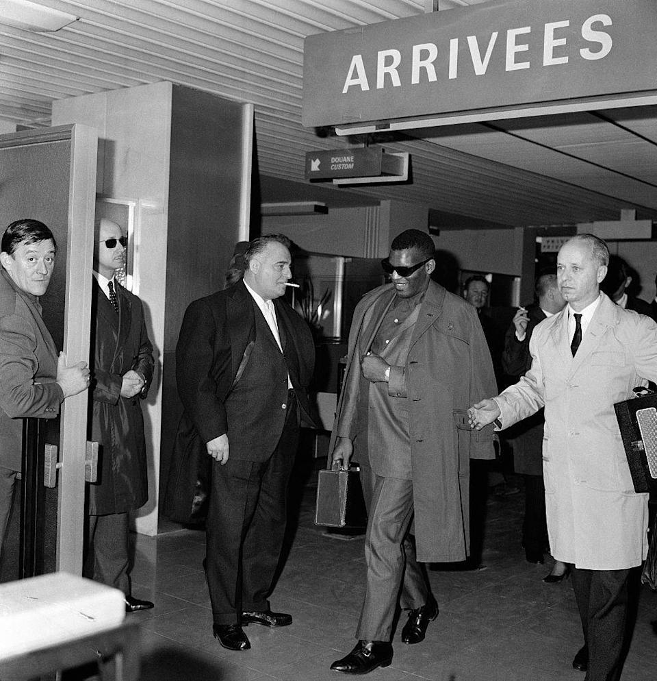 <p>L'Olympia's music director, Bruno Coquatrix, greets the musician at the Orly Airport before his performance the following night.</p>
