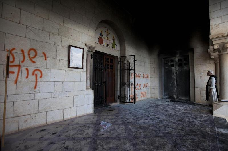 "A catholic priest looks at anti-Christian graffiti written in Hebrew at the Latrun Trappist Monastery where Israeli police say vandals overnight have spray-painted anti-Christian and pro-settler graffiti and set the monastery's door on fire, in Latrun, between Jerusalem and Tel Aviv, Israel, Tuesday, Sept 4, 2012. Suspicion fell on Jewish settlers and their supporters who retaliate against anti-settlement measures, generally by attacking Palestinian property, but also by vandalizing Christian sites and Israeli military facilities. Earlier this week, the government ordered settlers out of two unauthorized enclaves in the West Bank. Some of the graffiti referred to unauthorized settler outposts and one read, ""Jesus is a monkey."" (AP Photo/Oded Balilty)"