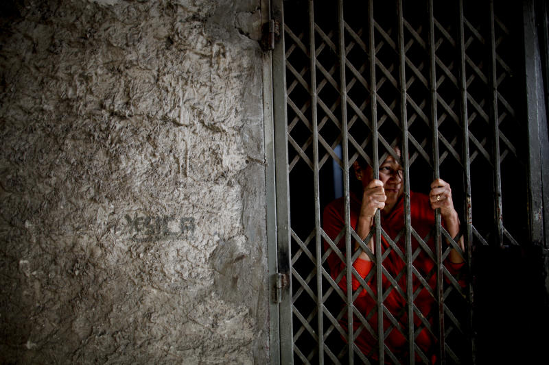 In this Sept. 6, 2018 photo, Modesta Cabanas stands behind her home's security gate on the outskirts of Buenos Aires, Argentina. Cabanas said she goes to the local soup kitchen to feed her family, and that since the economic crisis started, the meal portions are much smaller now that more people are eating there. (AP Photo/Natacha Pisarenko)