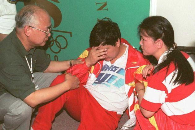 ATLANTA, GA - JULY 20:  China's Wang Yifu is attended by Chinese team officials after he collapsed during the shooting event at the Wolf Creek Shooting Complex, near Atlanta, 20 July. Wang, who was in the lead, missed his final shot and collapsed, to take silver. (FOR EDITORIAL USE ONLY) AFP/IOPP/Michel GANGNE  (Photo credit should read MICHEL GANGNE/AFP via Getty Images) (Photo: MICHEL GANGNE via Getty Images)