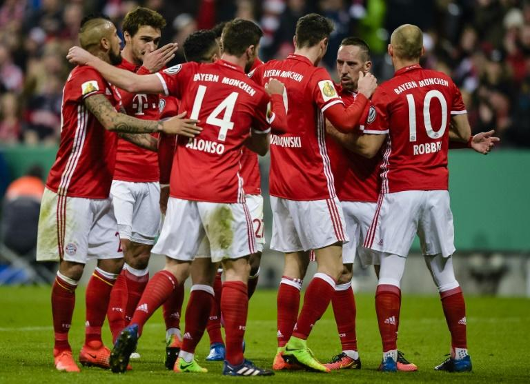 Bayern Munich's striker Robert Lewandowski (C) celebrates the third goal with teammates during the German Cup DFB Pokal quarter-final football match against Schalke 04 March 1, 2017