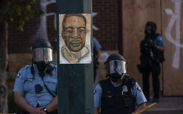 "<span class=""caption"">A portrait of George Floyd hangs on a street light pole as police officers stand guard at the Third Police Precinct during a face off with a group of protesters on May 27, 2020 in Minneapolis. </span> <span class=""attribution""><a class=""link rapid-noclick-resp"" href=""https://www.gettyimages.com/detail/news-photo/portrait-of-george-floyd-hangs-on-a-street-light-pole-as-news-photo/1215796055?adppopup=true"" rel=""nofollow noopener"" target=""_blank"" data-ylk=""slk:Stephen Maturen/Getty Images"">Stephen Maturen/Getty Images</a></span>"