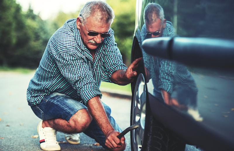Old man changing a flat tire