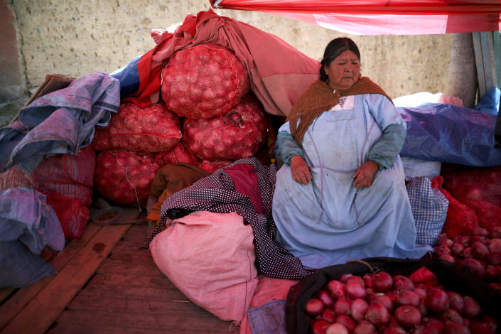 A woman sells onions at a market in La Paz, Bolivia, Monday, Nov. 18, 2019. Road blockades are causing food and fuel shortages in cities, particularly in the capital of La Paz. Residents in several Bolivian cities are reporting food and gasoline shortages because of protests by supporters of former President Evo Morales. (AP Photo/Natacha Pisarenko)