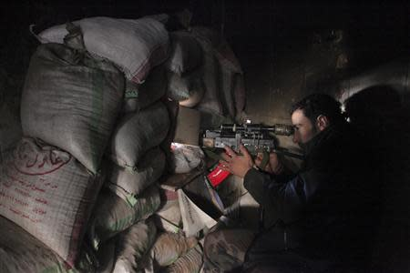 A Syrian army soldier loyal to Syria's President Bashar al-Assad points his weapon through piled sandbags at the Justice Palace in the old city of Aleppo, February 10, 2014. REUTERS/George Ourfalian
