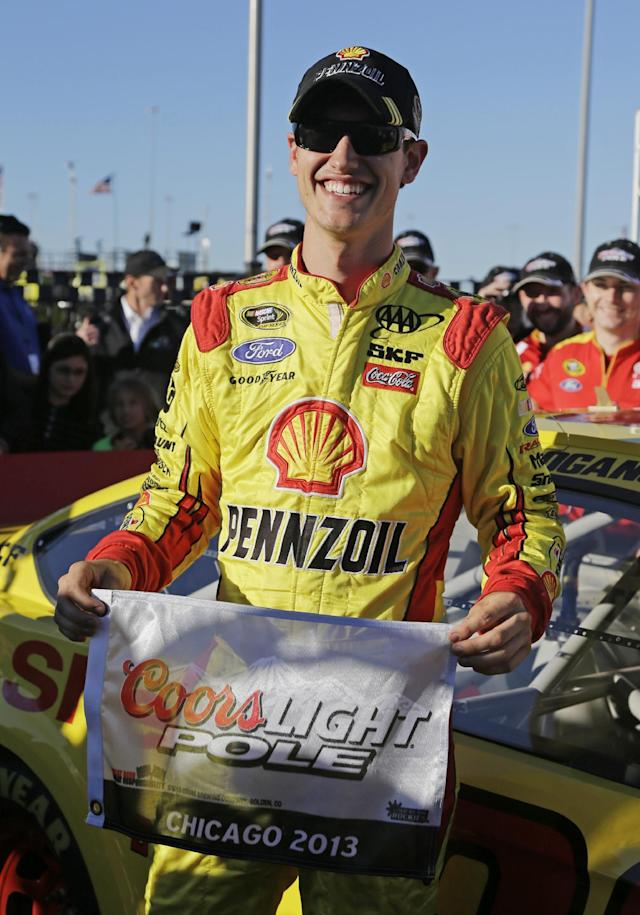 Joey Logano smiles after winning the pole during qualifying for the NASCAR Sprint Cup Series Geico 400 auto race at Chicagoland Speedway in Joliet, Ill., Friday, Sept. 13, 2013. (AP Photo/Nam Y. Huh)