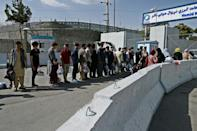 Afghans hoping to leave Taliban-controlled Afghanistan queue at the main entrance gate of Kabul airport (AFP/WAKIL KOHSAR)