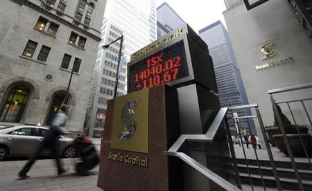 A man walks past an electronic board displaying the midday TSX index in Toronto