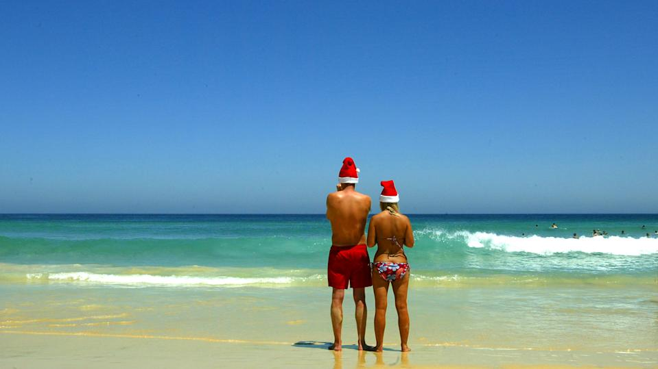 A pair of tourists wearing Christmas hats find a vacant stretch of water at Sydney's Bondi Beach on December 25, 2019.