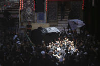 Mourners carry the coffin of Grand Ayatollah Sayyid Mohammed Saeed al-Hakim, inside the holy shrine of Imam Hussein during his funeral procession in Karbala, Iraq, Saturday, Sept. 4, 2021. Mohammed Saeed al-Hakim, one of Iraq's most senior and influential Muslim Shiite clerics, died at the age of 85. (AP Photo/Anmar Khalil)