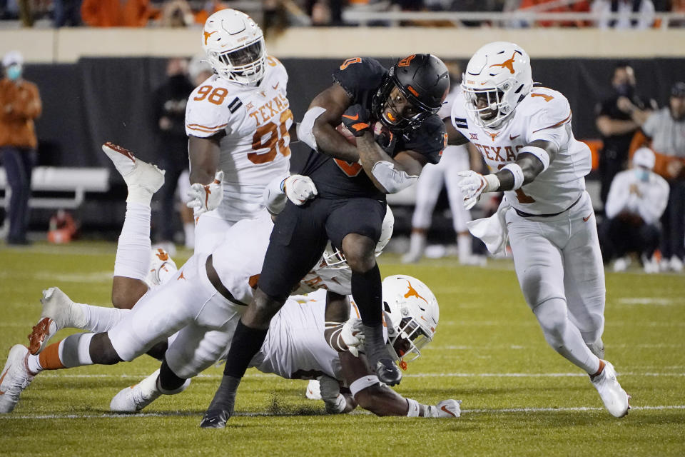 Texas defensive back Chris Adimora (1) moves in to tackle Oklahoma State running back LD Brown (0) in overtime of an NCAA college football game in Stillwater, Okla., Saturday, Oct. 31, 2020. (AP Photo/Sue Ogrocki)