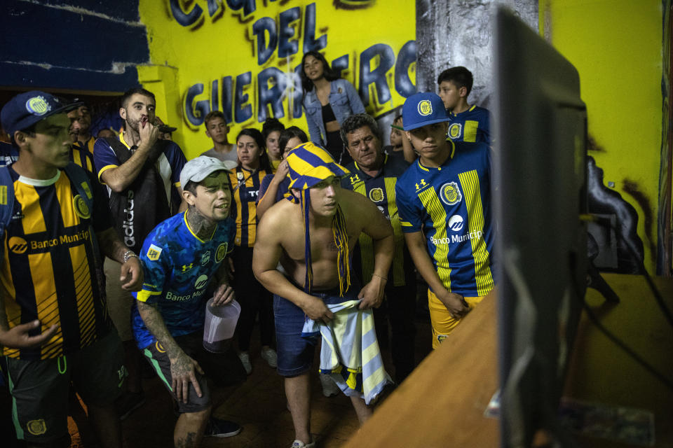 """Rosario Central soccer fan club members of """"Defensores de Tablada"""" watch their team's match against Newell's Old Boys on a home's back porch while fans are banned from attending games in person in Rosario, Argentina, Sunday, May 2, 2021. Few places in the world have soccer fans more passionate than those in Argentina, and few have been so long denied a live view of their teams due to the COVID-19 pandemic. (AP Photo/Rodrigo Abd)"""