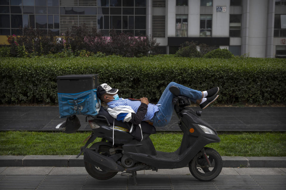 A delivery courier wearing a face mask to protect against the new coronavirus rests on his scooter in Beijing, Friday, July 3, 2020. Strict quarantine, social distancing and case tracing measures have helped radically bring down infections in China and mask wearing is still universal in indoor spaces, while many venues also require proof on a mobile phone app that the person is healthy. (AP Photo/Mark Schiefelbein)