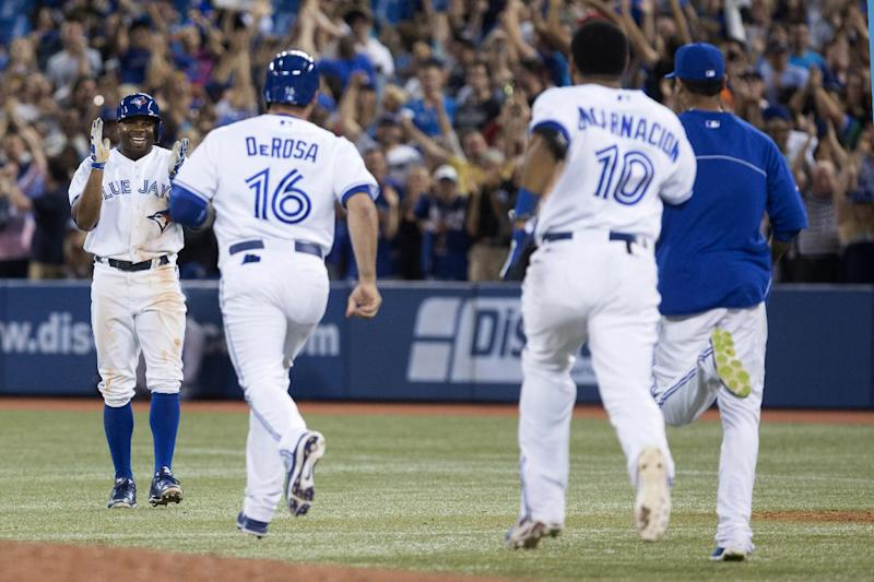 Toronto Blue Jays' Rajai Davis, left, turns to celebrate with on rushing teammates after hitting a game-winning single during the ninth inning against Baltimore Orioles baseball game in Toronto on Friday June 21, 2013. (AP Photo/The Canadian Press, Chris Young)