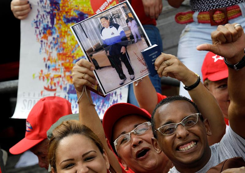 Supporters of Venezuela's President Hugo Chavez hold up a photo of him at an event commemorating the 1958 fall of the country's dictatorship in Caracas, Venezuela, Wednesday, Jan. 23, 2013. Chavez, who was re-elected to another six-year term in October, has not appeared or spoken publicly since he left for Havana on Dec. 10. Government officials have said the 58-year-old president is improving after suffering complications including a severe respiratory infection, but they have not provided specific details about his health. (AP Photo/Fernando Llano)