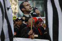 <p>Lawyers and magistrates hold a placard with a portrait of French President Emmanuel Macron during a demonstration as part of a nationwide day of protest against a government draft law on Justice, in Paris, Wednesday, April 11, 2018. (AP Photo/Francois Mori) </p>