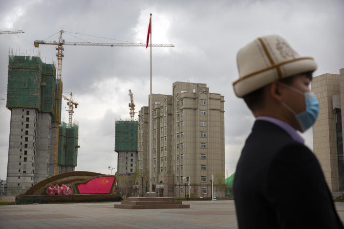 A man wearing a Kyrgyz hat stands on a plaza near a display with the Chinese flag at the Xinjiang Islamic Institute, as seen during a government organized visit for foreign journalists, in Urumqi in western China's Xinjiang Uyghur Autonomous Region on April 22, 2021. Under the weight of official policies, the future of Islam appears precarious in Xinjiang, a remote region facing Central Asia in China's northwest corner. Outside observers say scores of mosques have been demolished, which Beijing denies, and locals say the number of worshippers is on the decline. (AP Photo/Mark Schiefelbein)