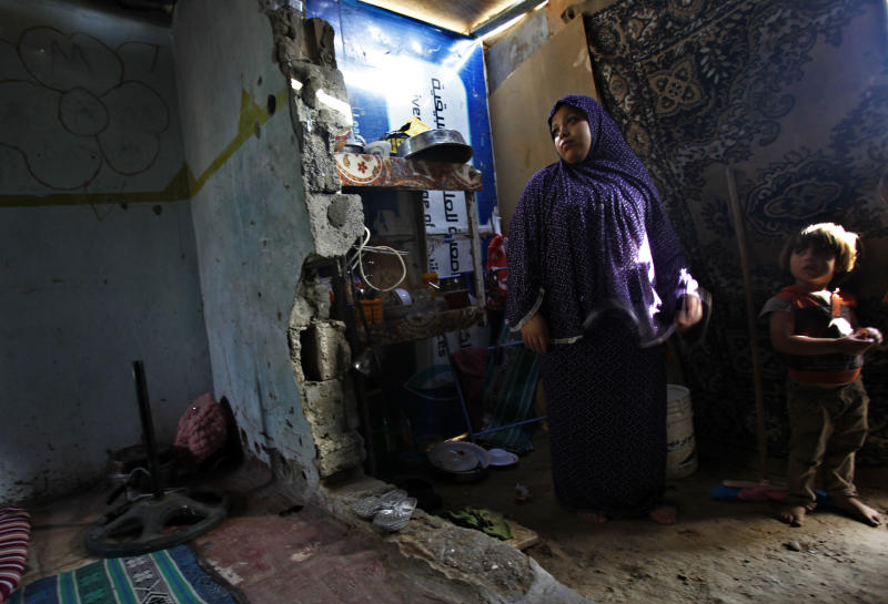 In this Thursday, Sept. 12, 2013 photo, Alyaa Alwadiya, 27, left, stands with her son Loai, 4, in the makeshift kitchen of their family house in Gaza City. Alwadiya's extended family is among Gaza Strip's poorest. They are not able to qualify for UNWRA assistance as they are not refugees. (AP Photo/Adel Hana)