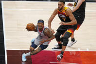 Washington Wizards guard Bradley Beal, left, drives to the basket as Utah Jazz center Rudy Gobert, right, defends in the second half during an NBA basketball game Monday, April 12, 2021, in Salt Lake City. (AP Photo/Rick Bowmer)