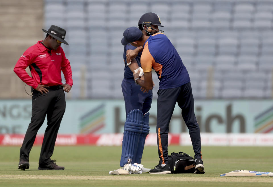 India's Rohit Sharma, center, is attended by team physiotherapist during the first One Day International cricket match between India and England at Maharashtra Cricket Association Stadium in Pune, India, Tuesday, March 23, 2021. (AP Photo/Rafiq Maqbool)