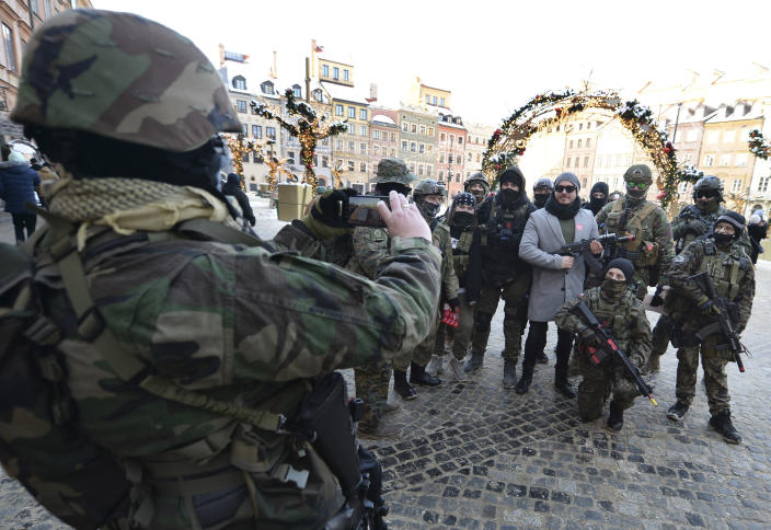 Military fans, dressed as soldiers and the charity's red heart symbol, pose for a photo as they collect money for Poland's most popular nationwide fundraiser for health purposes, the Great Orchestra of Christmas Charity, that was postponed by two weeks due to the pandemic, in downtown Warsaw, Poland, on Sunday, Jan. 31, 2021. Anti-government protesters angry about a near-total abortion ban suspended their marches for the weekend to show solidarity and ensure that they didn't steal the spotlight from the event. (AP Photo/Czarek Sokolowski)