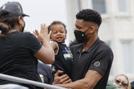 Milwaukee Bucks' Giannis Antetokounmpo, right, girlfriend Mariah Riddlesprigger and their son Liam ride on a bus during a parade for the NBA Championship Bucks basketball team Thursday, July 22, 2021, in Milwaukee. (AP Photo/Jeffrey Phelps)