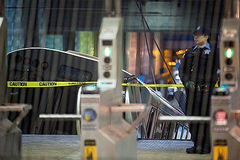 A police officer stands near a Chicago Transit Authority train car that derailed at the O'Hare Airport station early Monday, March 24, 2014, in Chicago. Photo: Andrew A Nelles/AP