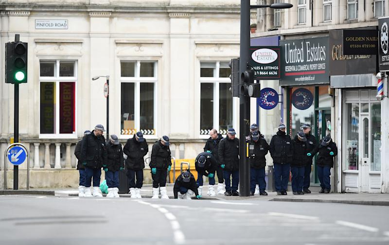 """Police officers conduct a search on Streatham High Road in south London on February 3, 2020, after a man was shot dead by police on February 2, following reports he had stabbed two people. - British police were searching two homes on Monday after shooting dead a convicted terrorist who knifed two people in a London street. Sudesh Amman, 20, who was wearing a fake suicide vest, was shot on a busy road in south London on Sunday after what police said was an """"Islamist-related"""" incident. (Photo by DANIEL LEAL-OLIVAS / AFP) (Photo by DANIEL LEAL-OLIVAS/AFP via Getty Images)"""