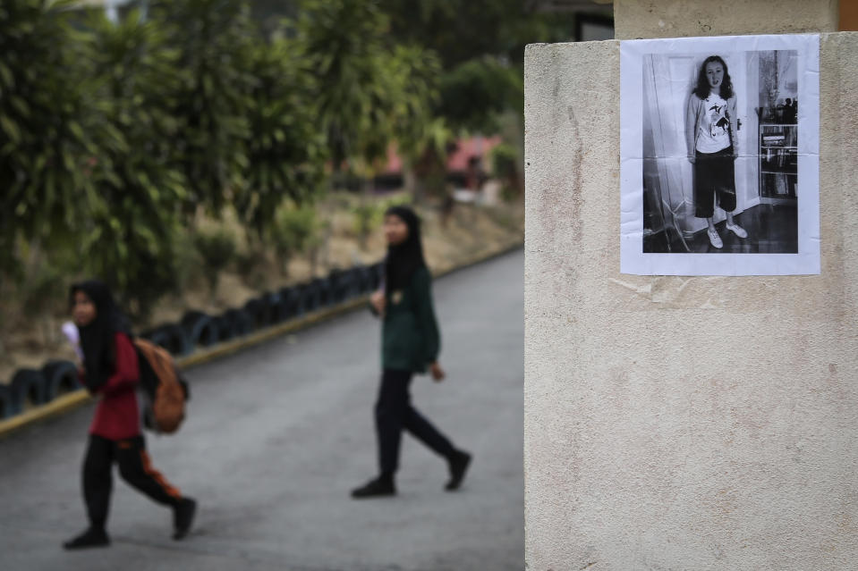 Students walk past a photo of missing British girl Nora Anne Quoirin placed on a pillar outside a school in Seremban, Malaysia, Wednesday, Aug. 7, 2019. Malaysian police said Wednesday that some fingerprints were found in a forest resort chalet where the 15-year-old London girl was reported missing four days ago, and that they do not rule out possible criminal element. (AP Photo/Annice Lyn)