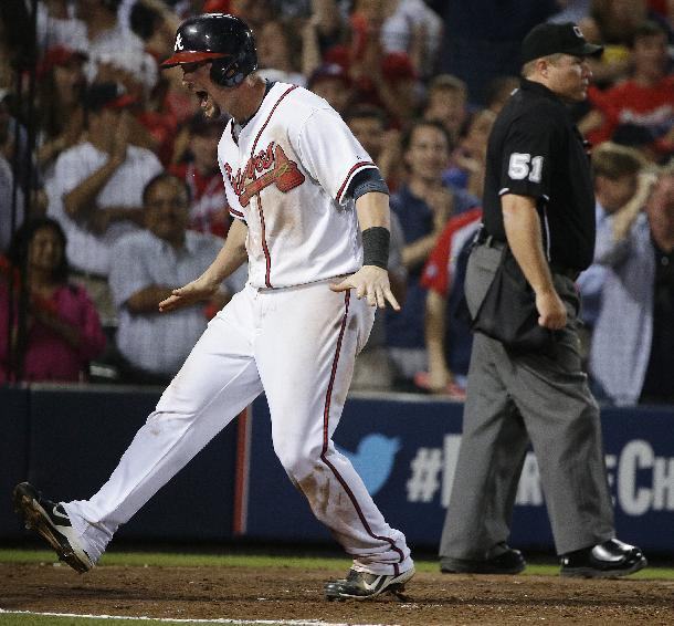 Atlanta Braves' Chris Johnson, left, celebrates after scoring on teammate Jason Heyward's single in the seventh inning of Game 2 of the National League division series against the Los Angeles Dodgers, Friday, Oct. 4, 2013, in Atlanta. (AP Photo/John Bazemore)