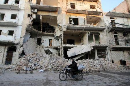 A man rides a motorcycle past damaged buildings in al-Myassar neighborhood of Aleppo, Syria January 31, 2016. REUTERS/Abdalrhman Ismail
