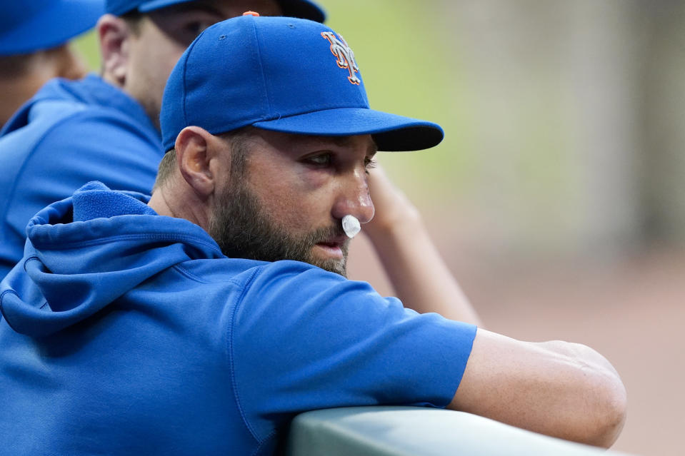 New York Mets' Kevin Pillar watches from dugout before the team's baseball game against the Atlanta Braves on Tuesday, May 18, 2021, in Atlanta. Pillar was hit on the face with a Jacob Webb fastball the night before. (AP Photo/John Bazemore)
