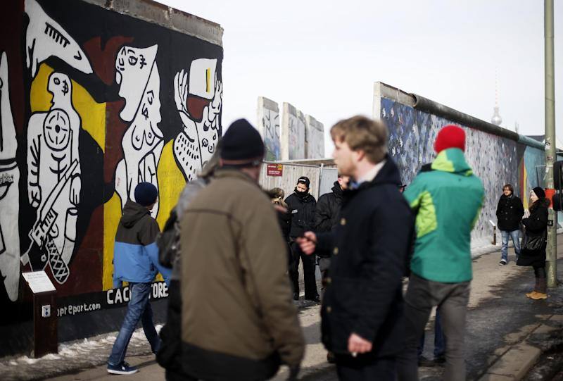 People gather in front of remaining parts of the Berlin Wall in Berlin on Wednesday, March 27, 2013. Work crews backed by about 250 police have removed portions of the Berlin Wall known as the East Side Gallery to make way for an upscale building project, despite demands by protesters that the site be preserved. Plans to remove part of the 1.3-kilometer (3/4-mile) stretch of wall sparked protests that developers were sacrificing history for profit. (AP Photo/Markus Schreiber)