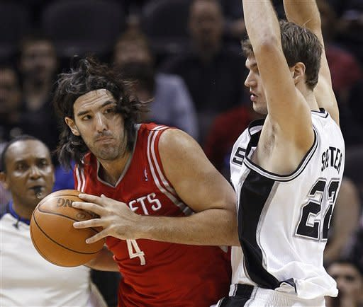 Houston Rockets' Luis Scola, left, of Argentina, looks around San Antonio Spurs' Tiago Splitter, of Brazil, during the first quarter of an NBA basketball game Wednesday, Jan. 11, 2012, in San Antonio. (AP Photo/Eric Gay)