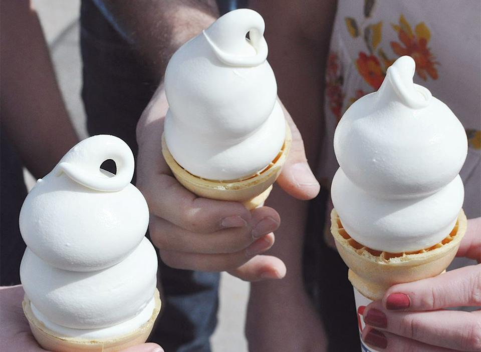 hands holding three soft serve ice cream cones dairy queen