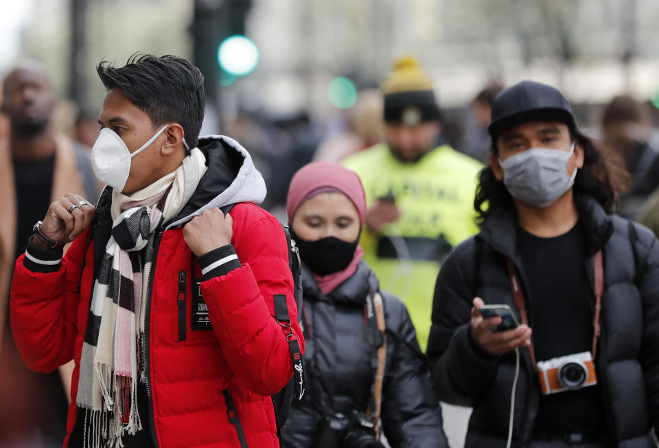People wearing face masks walk along Oxford Street in London, Saturday, March 14, 2020. For most people, the new COVID-19 coronavirus causes only mild or moderate symptoms, such as fever and cough. For some, especially older adults and people with existing health problems, it can cause more severe illness, including pneumonia.(AP Photo/Frank Augstein)